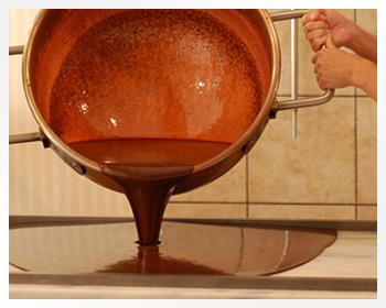 Pouring Fudge Out of a Large Copper Kettle