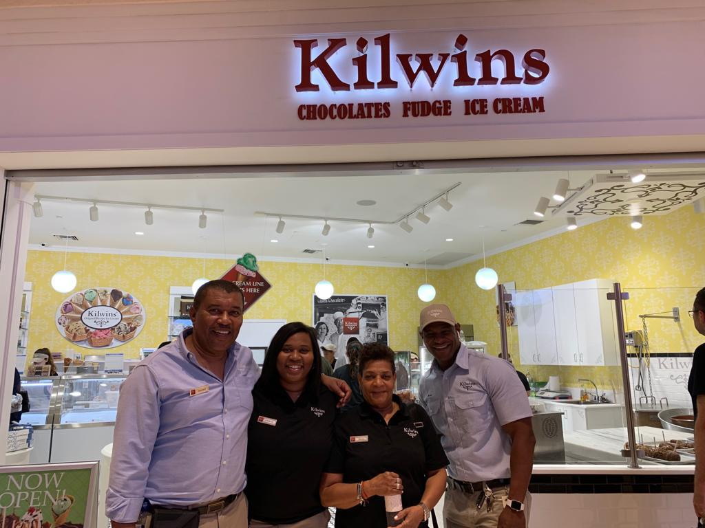Store owners standing in front of Kilwins Aventura storefront in Aventura Mall