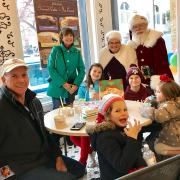 A picture of Santa and Mrs. Claus with a family at Kilwins