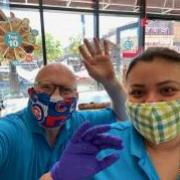 Photo of owner and team member waving wearing face masks