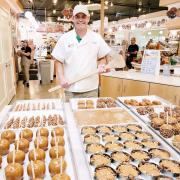 Owner in store wearing chef coat behind caramel-dipped items on table