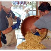 Photo of 2 men pouring Caramel Corn from copper kettle onto marble table