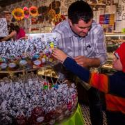 Photo of child selecting bagged candies from table with dad