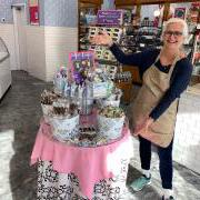 Photo of Team Member beside table of Kilwins products