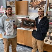 Photo of two men, one holding Kilwins 10 lb. Chocolate Bar and the other holding a bag of Kilwins treats