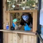 Photo of Team Member wearing gloves and mask serving Ice Cream Cone from walk-up window