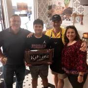 Picture of a family holding a 10lb Kilwins Heritage Chocolate bar