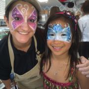 Photo of female team member and little girl with their faces painted