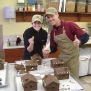 Picture of the owner and team member making ginger bread houses
