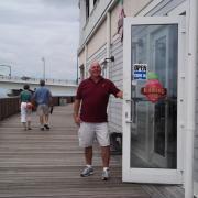 Photo of store owner opening door of Kilwins John's Pass on boardwalk
