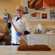 Photo of female Team Member behind loaf of Fudge