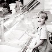 Black and white photo of little boy in front of Ice Cream Case