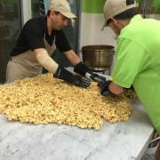 Photo of store owner and team member spreading Caramel Corn on marble table