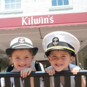 A picture of two children wearing Navy hats