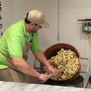 Photo of employee mixing Caramel Corn in copper kettle