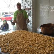 Photo of Team Member standing behind marble table filled with Caramel Corn