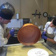 Photo of man and woman pouring Fudge from Copper Kettle on marble table