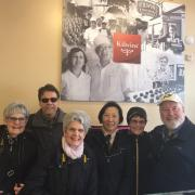 Photo of 6 adults smiling in front of Kilwins logo sign