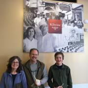 Photo of woman, man, & teenage boy standing in front of Kilwins logo sign