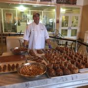 Photo of store owner with Caramel Apples & miscellaneous treats on marble table