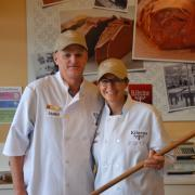 Photo of store owners smiling wearing chef coats