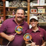Photo of man and woman holding lollipops