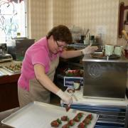 Photo of Team Member dipping strawberries in Chocolate