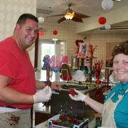 Photo of Team Members dipping strawberries in Chocolate