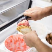 A picture of scooping ice cream for an ice cream cone