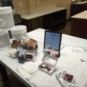 "Photo of misc. items on marble table: chef coat, ""Now Hiring"" sign, gift baskets, Chocolates, empty Ice Cream buckets"