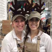Photo of 2 female team members wearing reindeer antler headbands
