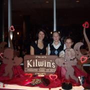 Photo of woman with two young girls behind Kilwins logo with Valentine's cupid display