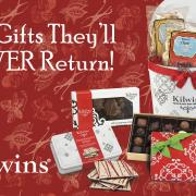 "Photo of array of Kilwins products: Tin of bagged Caramel Corn, box of Chocolates, Pepermint Bark, and Tuttles, with the text, ""The Gifts They'll NEVER Return!"""